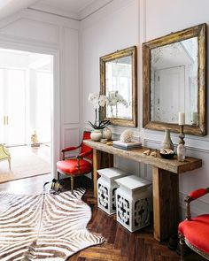 A pair of garden stools underneath a rustic wood console and a pair of distressed framed mirrors.