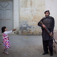 In this Nov. 15 2012 photo a young girl reaches out to greet a Pakistani policeman securing the road outside Kainat Riaz's home in Mingora Swat Valley Pakistan. Security stepped up after Kainat was wounded by the same Taliban gunman who shot Malala Yousufzai and 13-year-old Shazia Ramazan on Oct. 8 2012 on their way home from school. Malala was shot for her outspoken insistence on girls' education.  #APPhoto by Anja Niedringhaus  Two years ago Anja Niedringhaus an internationally acclaimed…