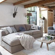 Rustige kleuren, stoere elementen en een personal touch met unieke meubels. De ruime bank is het middelpunt van deze woonkamer waar de hele familie samenkomt.
