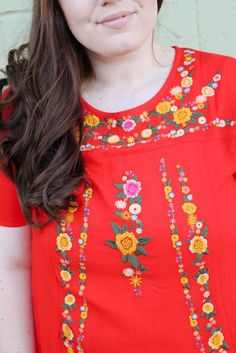 This fun top just SCREAMS summer! Red tunic with bright embroidered flowers and a relaxed fit. Light, breezy fabric. This colorful tunic is definitely the life