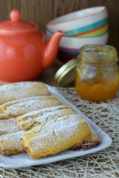 Le barrette di pasta frolla con marmellata d'arancia sono semplicissimi biscotti ripieni e spolverati con un leggero strato di zucchero a velo.