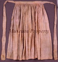 APRON, made of red and white calico cotton. The apron is a square with no bib, gathered into a waistband. Worn by one of the nurses at Winder Hospital during the war.