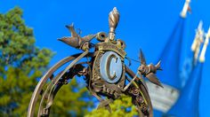 "A design atop a metal gate featuring two birds, the letter ""C"" and the name Cinderella"