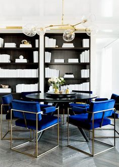 Dining space with a gold pendant light over a black table with blue velvet chairs