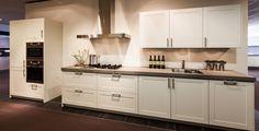 Deze tijdloze kadedeur is ook in 2016 weer in onze showrooms te bewonderen. Deze keuken is leverbaar in de kleuren kashmir, magnolia en wit. Hier is de keuken afgebeeld in de kleur wit, in dit geval niet gecombineerd met een zwart blad maar een beton-look blad van 6 cm dik. Hierdoor krijgt de keuken een moderne uitstraling.
