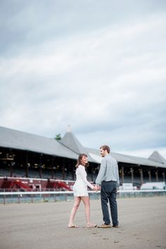 Cute couple take a stroll on the Saratoga Race Track during their Summer Engagement photos and I love the bride to be white romper!