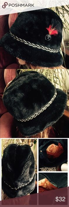 """Vintage UNISEX Black Faux Fur Hat w Ear Flaps This Vintage European style Black Faux Fur Hat has a black & white corded band encircling the brim, highlighted w/a decorative black button topped w/a feather. Inside has a gold satiny quilted lining & a pull-down ear/neck flap. Warm & comfy! No makers tag. Smoke-free home. In excellent preowned condition. Tagged XL. Inside circumference measures 23""""; crown height 7""""; 10"""" in diameter. Mannequin for display only & not reflective of how your hat…"""