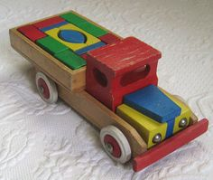 HEROS Wood Truck made in Germany. Bright primary colors of blue, red & yellow, metal headlights and hubcaps, sturdy rubber wheels, the truck is filled with wooden block and can be taken apart. All pieces are complete *CONDITION: great condition, great patina, well played with but many