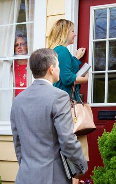 Una señora observa desde su ventana a unos testigos de Jehová que están llamando a su puerta