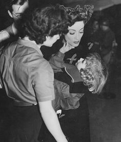 Joan Crawford humming to one of the children who plays scenes with her on the set of Reunion in France, 1942