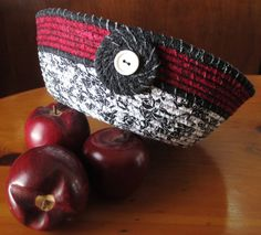 This black, burgundy and white basket is made from strips of fabric that is wrapped around clothesline. The fabrics raw edges frey to give it a rustic look. It measures approximately 6 1/2 wide at the base, 10 wide at the top and 3 1/4 high.    Spot cleaning recommended~Do not put in the washing machine