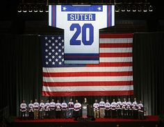 1980 USA Miracle on Ice hockey team 35th reunion. The remaining players gather under Bob Suter's jersey at Lake Placid.