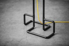 Detail of the Roboto floor lamp. Here in black patina metal finish with yellow braided cord on concrete flooring.