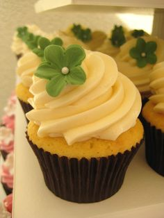 Vanilla cupcake with swirls of vanilla buttercream, topped with a handmade leafy green sugar flower.