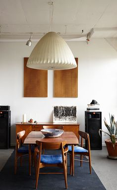 One of Owen's many hobbies is watercolor painting; the black and white painting seen here is one of his own. It sits just below a pair of decorative wall-hung particle boards. The credenza is a 1950s Renzo Rutili design for Johnson Furniture; the hanging lamp is by George Nelson. The dining room table and chairs are Danish-made midcentury teak models.