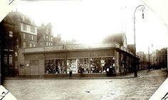 1909 Het hulpmagazijn van De Bijenkorf op het Damrak gezien naar de Dam. Links op de achtergrond de huizen aan de Beursstraat