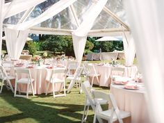 """66"""" Round Guest Tables and White Resin Chairs under 30x60 Clear Top Tent. Cafe lights and swag draping in a wheel style"""