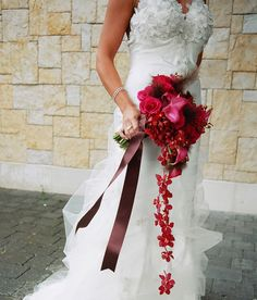 A hand-tied bouquet accompanied by wired, cascading orchids.