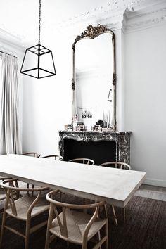 salle à manger blanche aménagée avec une belle cheminée en pierre et décorée d'un grand miroir vintage mouluré