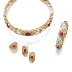 Ruby, mother-of-pearl and diamond parure, Mouawad Comprising: a choker of scale motif, set with cabochon rubies, brilliant-cut diamonds and mother-of-pearl, inner circumference approximately 330mm, a bangle, inner circumference approximately 150mm, a ring, size 501/2, and a pair of ear clips, each piece except one ear clip signed Mouawad, numbered, French assay and maker's marks.