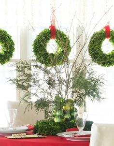 Top your Christmas table with a quick, easy and festive holiday centerpiece.    Centerpiece of Greens:   A clear container nestled in a green wreath holds bright green ornaments and a spray of mixed evergreens, all set off by a red tablecloth. Matching green wreaths hang in the dining room window.