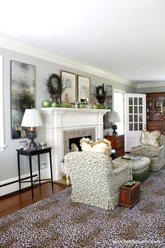 Living room | Mirrored panels frame the fireplace, complete with oversized ornaments. Classic style with European influence.