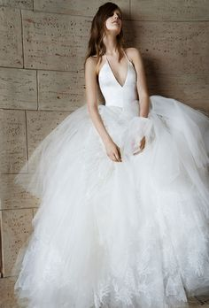 Brides.com: . Trend: Cool Tulle Skirts. Sleeveless silk charmeuse halter ball gown wedding dress with a deep v-neckline and full tulle skirt with Chantilly lace applique details, Vera Wang