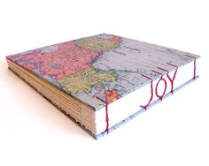 Journal with coptic stitched words on spine, JOY. Etsy site has other custom spine designs.