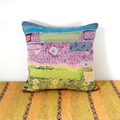 lovely kantha cushion cover in great colours - made from a truly old and worn kantha quilt with lots of patches! the pillow case is adorned with some yellow vintage pompom trim. please note - the kantha quilt that I used for this cushion shows quite a bit of wear and disintegrating sari layers. I personally love this shabby look!  measurements: about 40 x 40 cm (15.5 x 15.5 inches)  the pillow case comes without the insert.  care instructions: hand-wash in warm water.  please note that the…