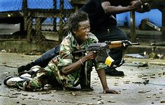 A government soldier defends a bridge in central Monrovia where a standoff between rebel and government forces held the city under siege. Carolyn Cole