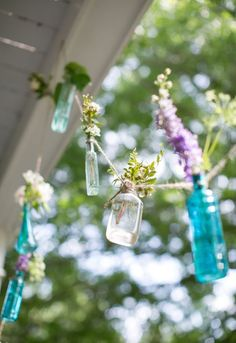 I melt for these vintage bottles strung with colorful wildflowers across the front of the house -- who knew a garland made of bottles could be so cute? #cedarwoodweddings Whimsical Watercolor Wedding at Historic Cedarwood | Cedarwood Weddings