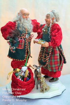 """Mr. and Mrs. Elvin Santa Claus 13"""" tall made from cernit polymer clay over a wire armature. Their handmade costumes are made from velour, leather and ribbons. Vintage jewelry adorns their clothing and one special piece is in Mrs. Santa's hair. Santa's bag holds a polymer clay elf doll, a baseball and bat and other goodies.  A young mule deer doe and a gold lab wearing Christmas charms wait at their feet. """"Merry Christmas"""""""