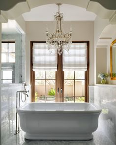 A beautiful crystal chandelier and sitting tub create a relaxing and spa-worthy setting in the master bathroom.
