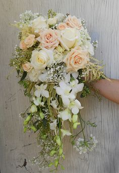 Peach and white cascade bridal bouquet with sahara roses, astilbe, orchids, white roses, and touches of babies breath #PeachCascadeBouquet #CascadeBridalBouquet