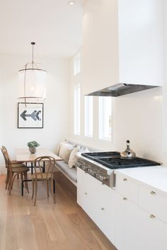Beautiful light and airy kitchen - bright white cabinets softened with wood floors and traditional wood dining chairs. Also retro pieces around the rest of the house. Contemporary but also a bit boho. Love!