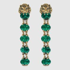 Made in metal with aged gold finish, Gucci's lion head earrings hold a green faceted Swarovski crystal in its mouth which extends to a drop of more faceted crystals.