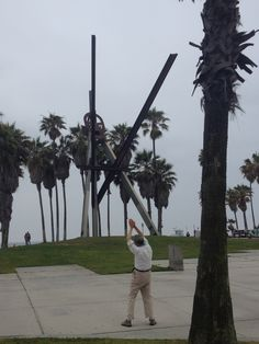 Asian man doing Tai Chi at the base of the sculpture