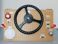 Homemade Dashboard: Pegboard, old steering wheel, bubble light, switches, buttons, & levers.
