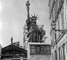 The Statue of Liberty as she towers above the streets of Paris. She was disassembled and shipped to New York in 1885 before her dedication in 1886
