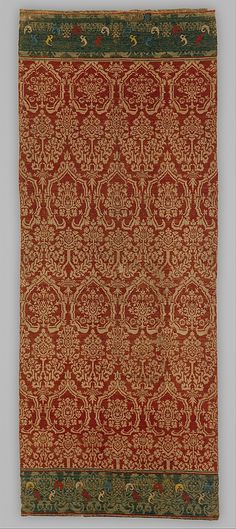 Wall Hanging, with Pomegranate Pattern Date: early 16th century  Geography: Made in Nuremberg, Germany Medium: Twill binding: linen warp, and weft in red, white, green, blue, and yellow wool, with metallic threads  Dimensions: Overall: 96 x 40in. (243.8 x 101.6cm) Framed: 110 1/2 x 47 x 4 3/4 in. (280.7 x 119.4 x 12.1 cm) Accession Number: 53.35.2 The Metropolitan Museum of Art