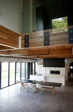 Douglas-fir beams, concrete floors and exposed ductwork give the 4,410 square-foot interior a loft feel. The balcony's Plexiglas half-wall allows light from the street-facing window to wash upstairs and down. The Buchanan-designed stone table will soon be joined by the rest of the family's furniture.