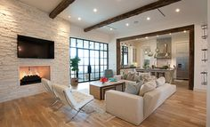 Popular paint colour for staging or selling is Glacier White by Benjamin Moore.  Shown in living room with light wood floors, stacked stone fireplace and wood beams