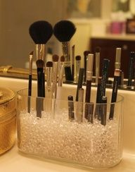 Glass beads in a clear glass vase to hold makeup brushed and eyeliners.