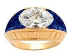 A Van Cleef & Arpels ring of 18k gold with invisibly set blue sapphires and an oval cut diamond.