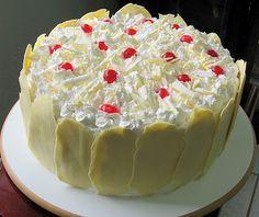 Bolo de festa - aniversário, etc- boloTrufado Maravilhoso - massa branca, recheio de abacaxi e trufa de chocolate branco, cobertura de ganache branca (ou chantilly)  e 'pétalas' de chocolate branco.