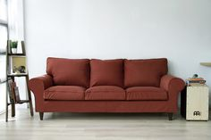 Rust-red woollen snug fit tailored sofa covers made by Comfort Works, on an IKEA Ektorp 3 seater sofa, with replacement custom stained Walker wooden sofa legs.