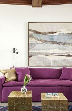 """The painting above the berry-hued Verellen sofa in the living room was brought over from the client's previous house. """"I'd been digging around and I found it from a dealer. It's by a Japanese artist, from the 40s or 50s,"""" says Hranowsky. """"It's really big and really beautiful. I knew instantly that we would hang it in the living room where all those wooden beams are."""" An indigo blue rug by Woven Accents ties in with the artwork perfectly. The pair of brass tables are by Sarreid…"""