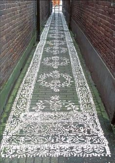 Narrow space between buildings painted to look like a rug.