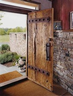 Two inch thick oak barn threshing floor boards and custom hand forged hardware become stout front entrance door. Original red barn siding reused as interior wall treatment. Love thick wooden doors and stone!