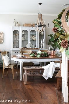 Magnolia garland and other simple greenery and hints of mercury glass create a lovely French farmhouse style Christmas dining room.